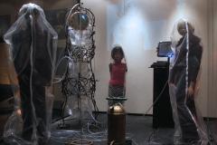 Sa izložbe 'Umetnički/veštački život – Kuntlih/Kunstlerich Leben', kafe-galerija Kocka, 2006.(instalacija lutaka koje su prikačene na bocu sa kiseonikom u staklenoj kocki)